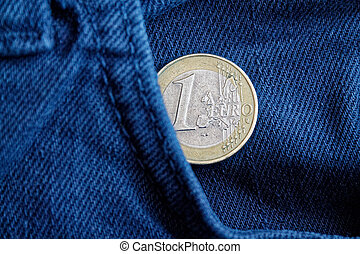 Euro coin with a denomination of 1 euro in the pocket of worn old blue denim jeans