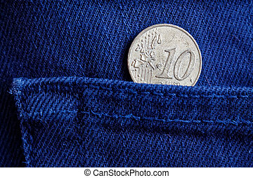 Euro coin with a denomination of 10 euro cent in the pocket of blue denim jeans