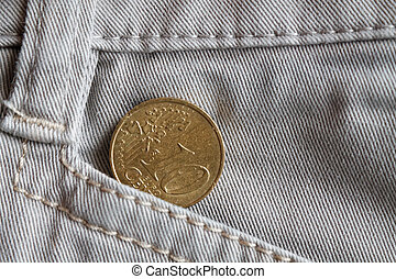 Euro coin with a denomination of 10 euro cents in the pocket of white denim jeans