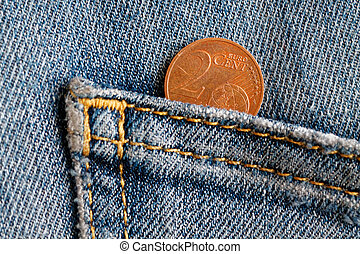 Euro coin with a denomination of 2 euro cent in the pocket of old blue denim jeans