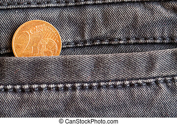 Euro coin with a denomination of 2 euro cent in the pocket of worn blue denim jeans
