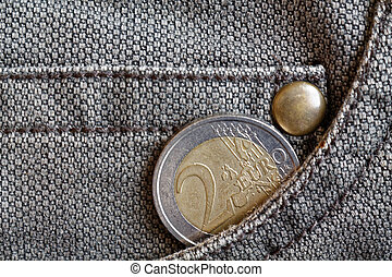 Euro coin with a denomination of 2 euro in the pocket of worn brown denim jeans