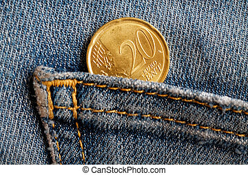 Euro coin with a denomination of 20 euro cents in the pocket of blue worn denim jeans