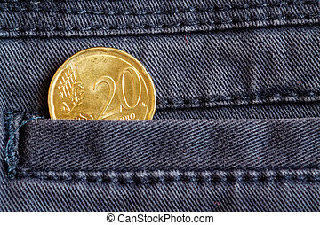 Euro coin with a denomination of 20 euro cents in the pocket of dark blue denim jeans