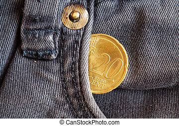 Euro coin with a denomination of 20 euro cents in the pocket of obsolete blue denim jeans