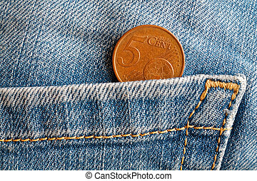 Euro coin with a denomination of 5 euro cents in the pocket of light blue denim jeans