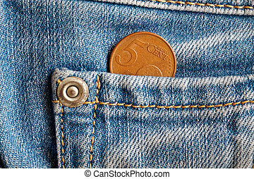 Euro coin with a denomination of 5 euro cents in the pocket of old blue denim jeans