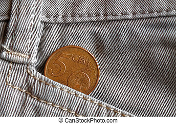 Euro coin with a denomination of 5 euro cents in the pocket of white denim jeans