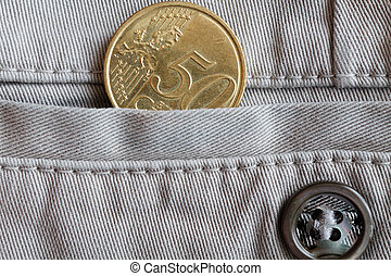 Euro coin with a denomination of 50 euro cents in the pocket of beige denim jeans with button