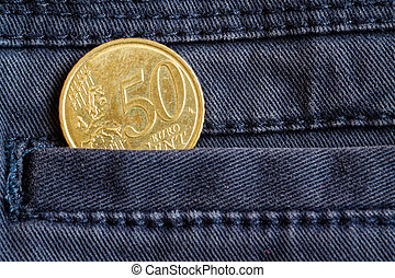 Euro coin with a denomination of 50 euro cents in the pocket of dark blue denim jeans
