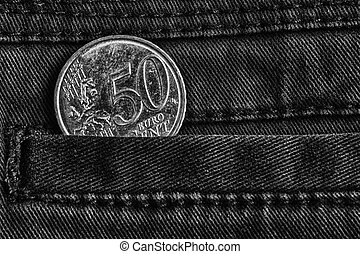 Euro coin with a denomination of 50 euro cents in the pocket of dark denim jeans, monochrome shot