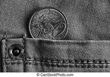 Euro coin with a denomination of 50 euro cents in the pocket of denim jeans, monochrome shot