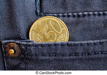 Euro coin with a denomination of 50 euro cents in the pocket of gray denim jeans