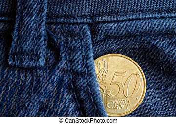 Euro coin with a denomination of 50 euro cents in the pocket of old blue denim jeans