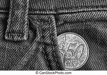 Euro coin with a denomination of 50 euro cents in the pocket of old denim jeans, monochrome shot