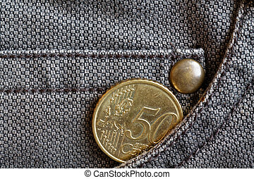 Euro coin with a denomination of 50 euro cents in the pocket of worn brown denim jeans