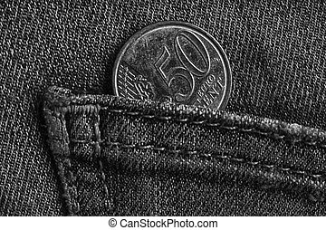 Euro coin with a denomination of 50 euro cents in the pocket of worn denim jeans, monochrome shot