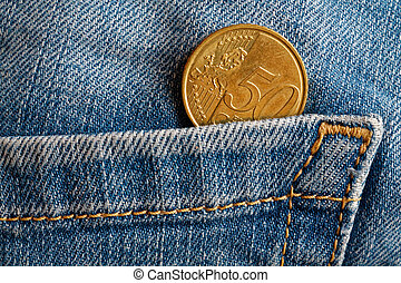 Euro coin with a denomination of fifty euro cents in the pocket of old blue worn denim jeans