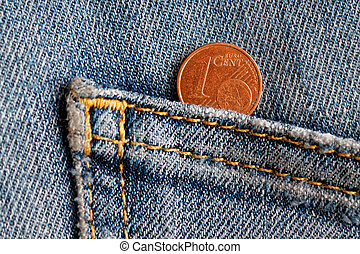 Euro coin with a denomination of one euro cent in the pocket of old blue denim jeans