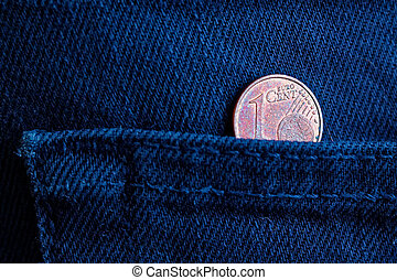 Euro coin with a denomination of one euro cent in the pocket of old dark blue denim jeans