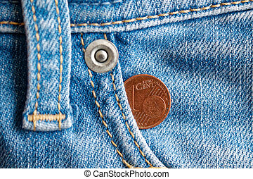Euro coin with a denomination of one euro cent in the pocket of old worn vintage blue denim jeans