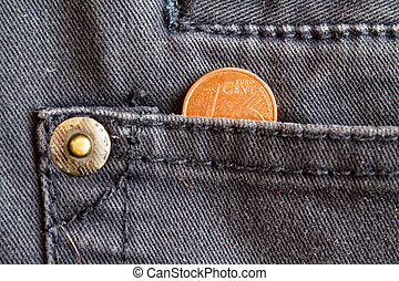 Euro coin with a denomination of one euro cent in the pocket of worn blue denim jeans