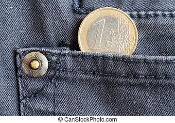 Euro coin with a denomination of one euro in the pocket of dark blue denim jeans