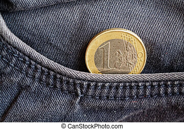 Euro coin with a denomination of one euro in the pocket of obsolete blue denim jeans