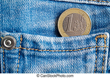 Euro coin with a denomination of one euro in the pocket of old worn blue denim jeans