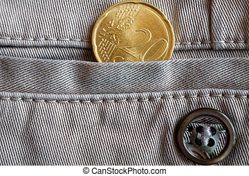 Euro coin with a denomination of twenty euro cents in the pocket of beige denim jeans with button