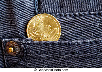 Euro coin with a denomination of twenty euro cents in the pocket of dark blue denim jeans