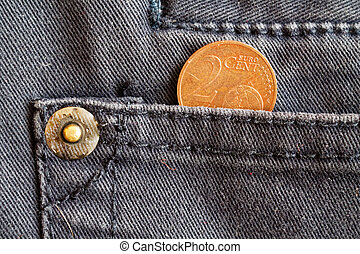 Euro coin with a denomination of two euro cent in the pocket of dark blue denim jeans