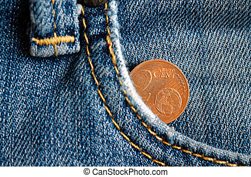 Euro coin with a denomination of two euro cent in the pocket of obsolete blue denim jeans