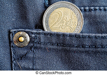Euro coin with a denomination of two euro in the pocket of blue denim jeans