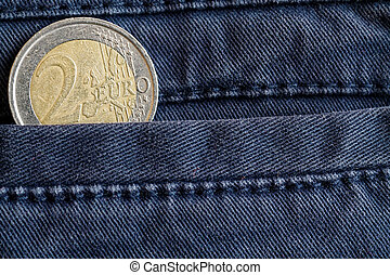 Euro coin with a denomination of two euro in the pocket of old blue denim jeans