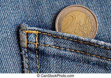 Euro coin with a denomination of two euro in the pocket of vintage blue denim jeans