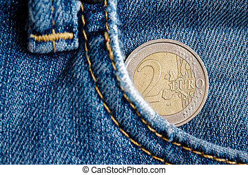 Euro coin with a denomination of two euro in the pocket of vintage worn blue denim jeans