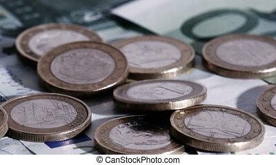 Euro coins falling down on euro banknotes