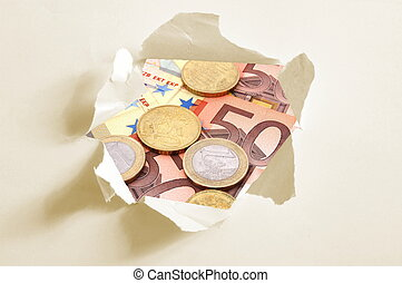 euro money behind hole in paper showing business and finance...
