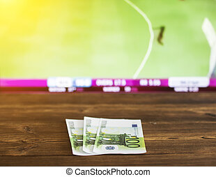 Euro money on the background of the TV on which there is a sports game of cricket, sports betting, euro
