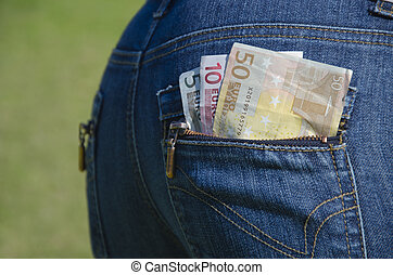 Euro money peeping out of a blue jeans back pocket