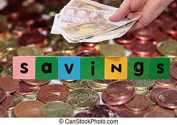 euro note and coins savings in toy letters
