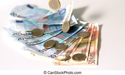 Euro notes and coins falling on wh - Euro notes and coins...