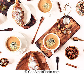 Perfect breakfast of croissant and coffee on wooden table. Rustic style. Top view.