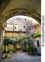 Sun-filled european-style courtyard with arched entry with ferns, vines and hanging plants, with a beautiful water fountain complete with lions head on the center wall.