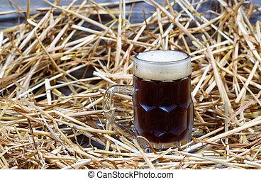 European Dark Beer in Stein on Straw and wood