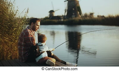 European father and son sit together on lake pier. Boy holds...
