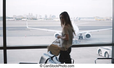 European female tourist walks up to airport lounge terminal window, puts her bag down and looks at airplanes passing.