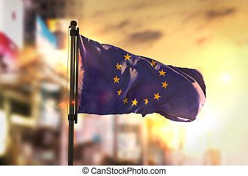 European Flag Against City Blurred Background At Sunrise Backlight