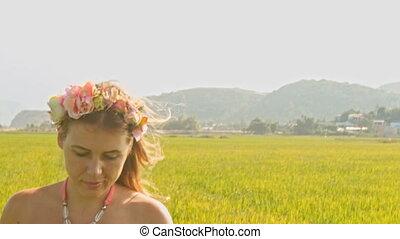 European Girl in Garland Walks Smells Rose Sits down on Grass